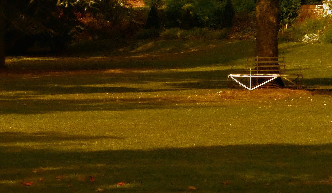 Circular white metal park bench in autumn