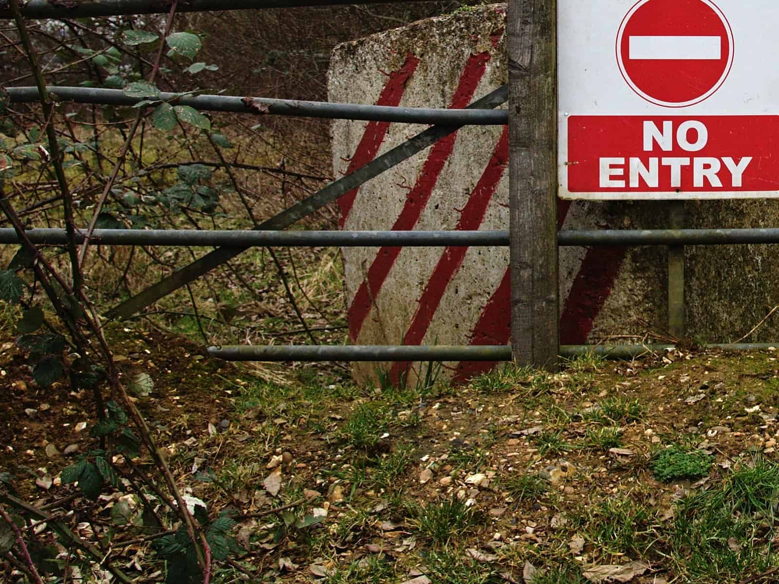 Photo: a no entry sign and a concrete road block