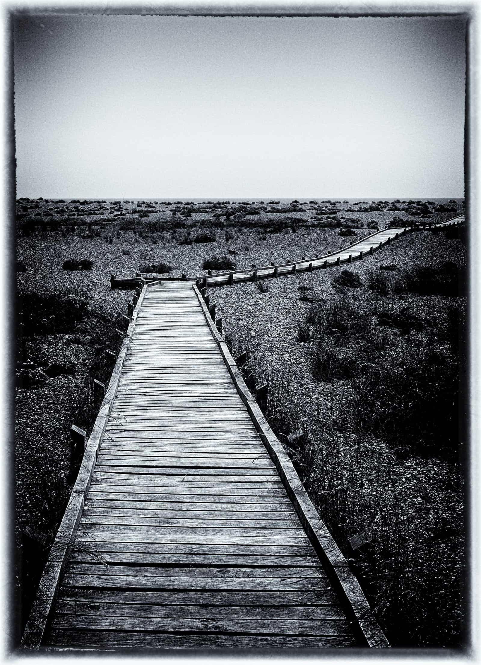 A wooden walkway across sand/shingle