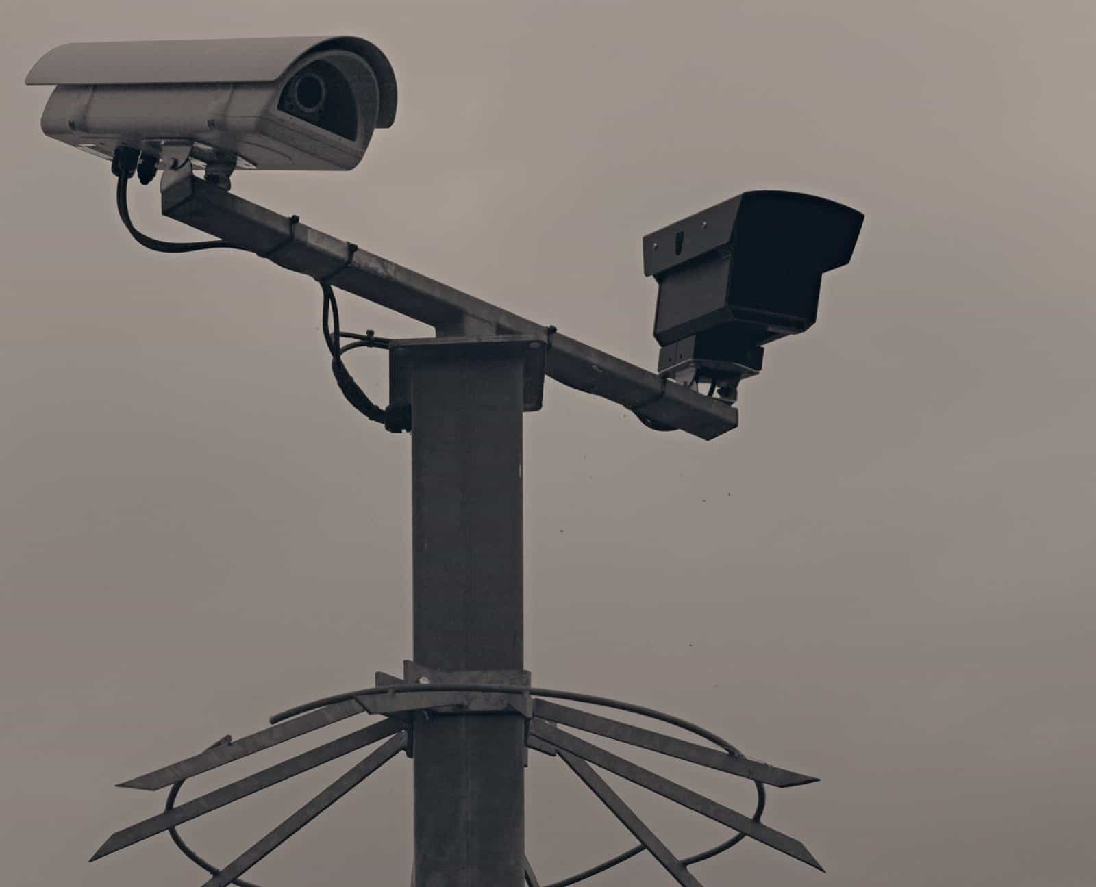 Two surveillance cameras mounted on a protected pole