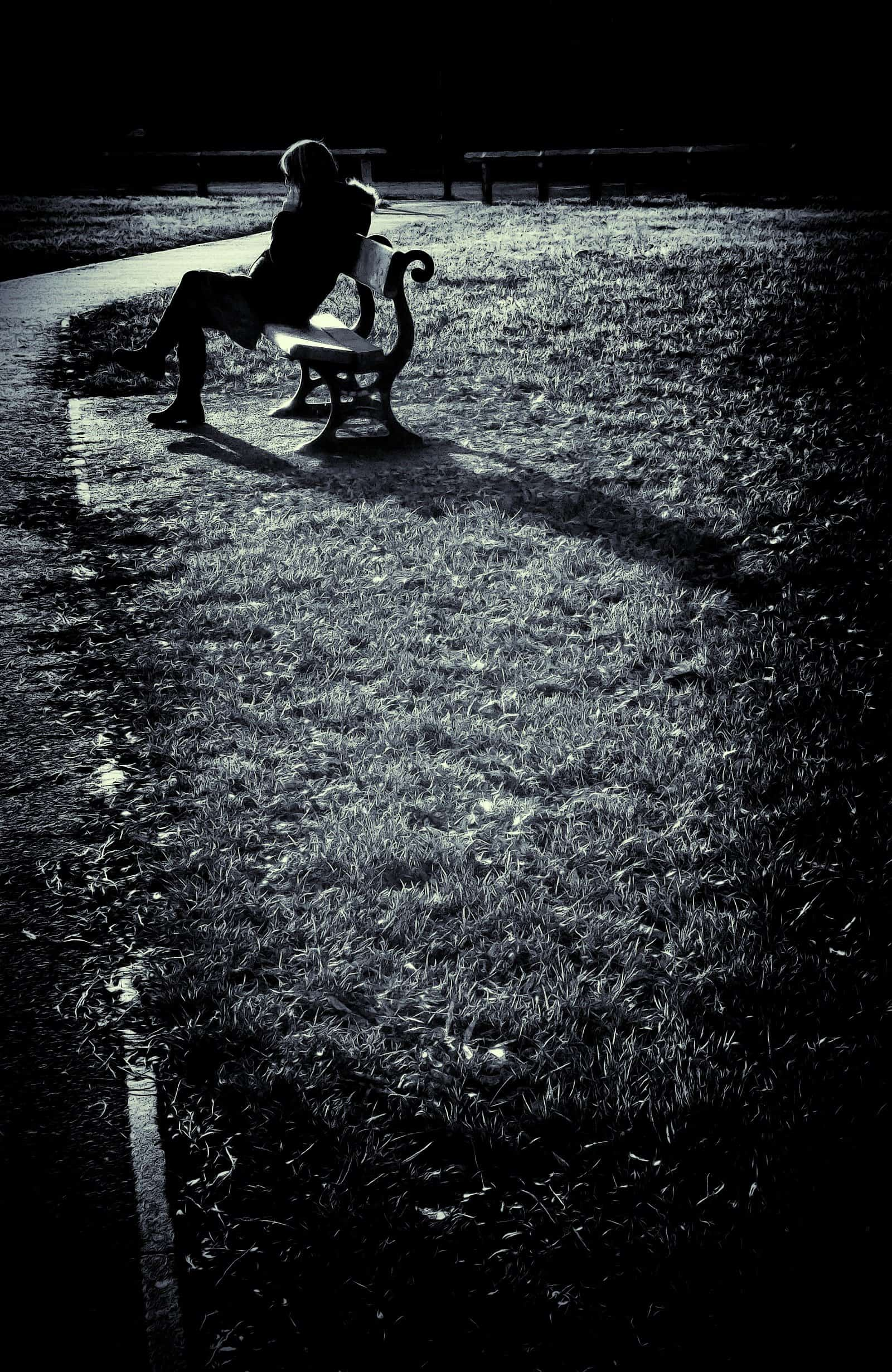 Someone sitting alone on a park bench